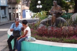 Man with guitar statue and locals